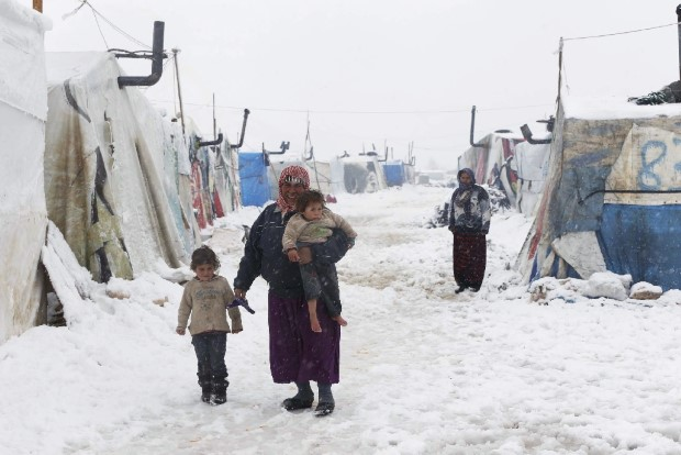 A Syrian refugee holds a barefoot child as she walks with a girl during snowfall at a refugee camp in Zahle